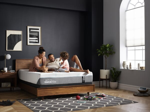 family on Tempur-Pedic mattress on wood bed frame in room shot